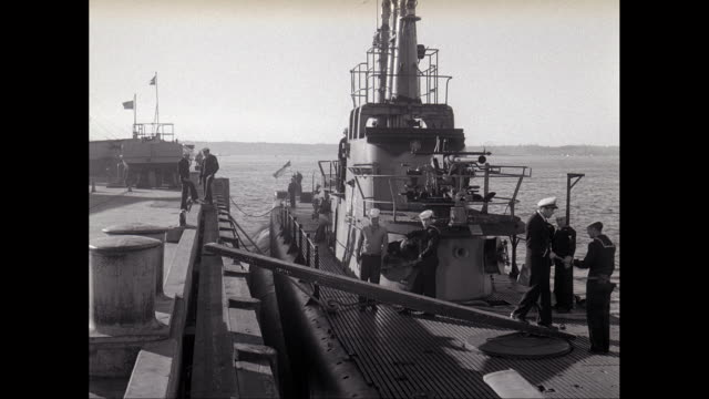 WS Officer approaches docked submarine with sailors on deck / United States