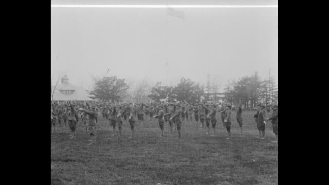 vídeos de stock, filmes e b-roll de us officer candidate school trainees stand in field as they train for service in wwi / trainees participate in calisthenics drill / trainees march /... - campo de treinamento militar