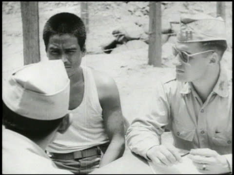 S officer Japanese interpreter interviewing Japanese prisoner of war in camp for intelligence about surrendering WWII World War II Pacific Front POW...