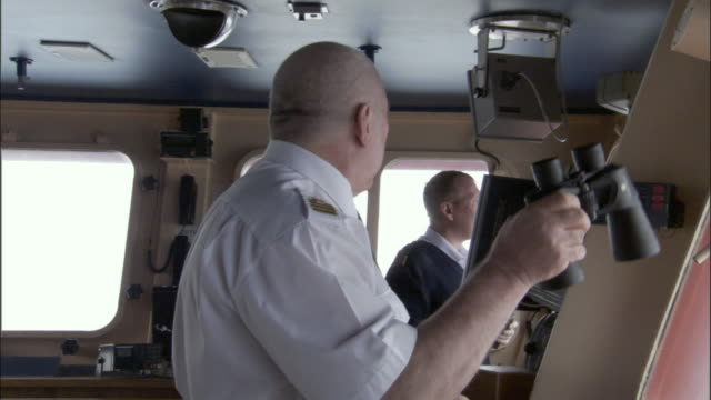vidéos et rushes de cu, zi, officer looking through binoculars in navigation bridge, russia - équipage de bateau