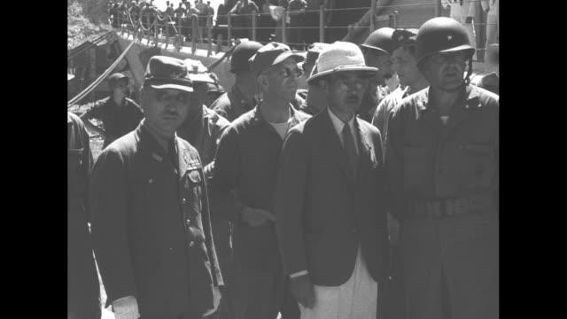 officer walks with japanese vice admiral michitaro tozuka at yokosuka naval base in japan during world war ii / tozuka approaches, passes / tozuka... - 軍事基地点の映像素材/bロール