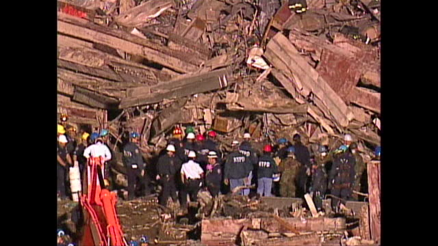 NYPD officers and first responders sift through the rubble of Ground Zero for survivors of the attacks on September 11th