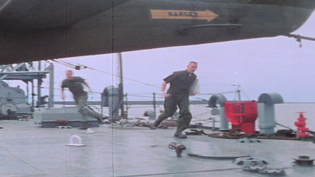 Officers heading to the bridge flight crew shrugging into flak vests and Mae Wests deck crew releasing chopper rotor during alert aboard USS Harnett...