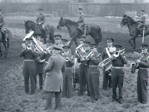 Officers of the Household Cavalry ride their horses past a brass band to get them used to loud noise