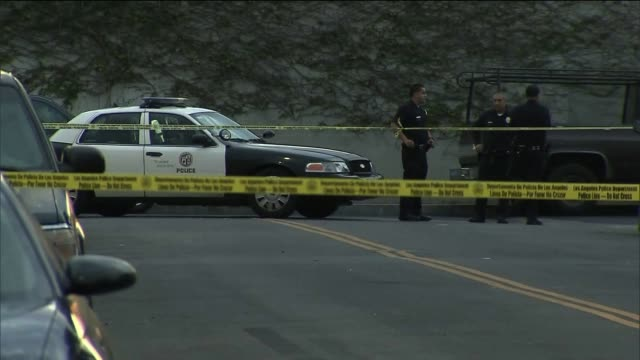 officers stand behind police tape and investigate shooting on september 03 2013 in los angeles california - 銃撃事件点の映像素材/bロール