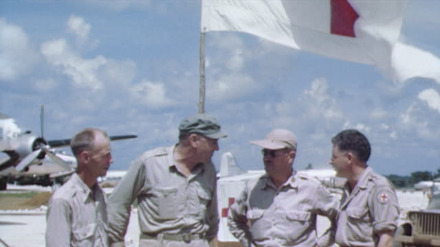 officers standing and conversing near a grounded c-54 aircraft as red cross flags are waving at yontan airfield / okinawa, japan - 陸軍点の映像素材/bロール