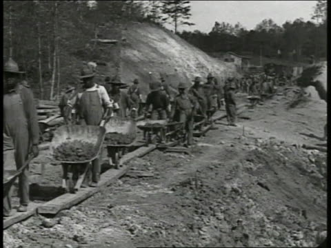 official car driving onto construction site africanamerican black men clearing area w/ wheel barrows ha pan construction site w/ lumber logs on... - 1917 stock videos & royalty-free footage