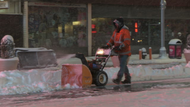 A DOT official is pushing a snow blower through Time Square during a snowstorm