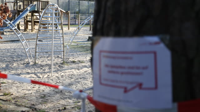 a official sign with the inscription that all playgrounds in berlin are concluded for an indefinite period following a city ordinance temporarily... - geschäftliche aktivitäten stock-videos und b-roll-filmmaterial