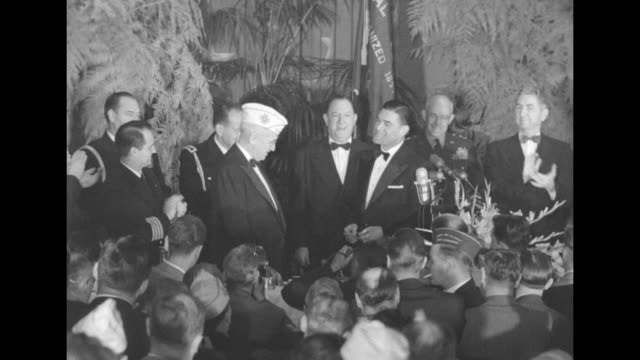 VFW official standing at lectern on head table hands VFW cap to Pres Harry Truman other officials at head table stand and applaud / Truman puts cap...