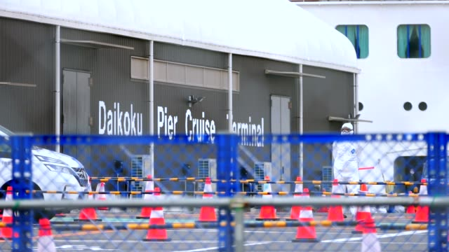 officials in protective suits work near to the quarantined cruise ship diamond princess anchored at the daikoku pier cruise terminal in yokohama,... - anchored stock videos & royalty-free footage