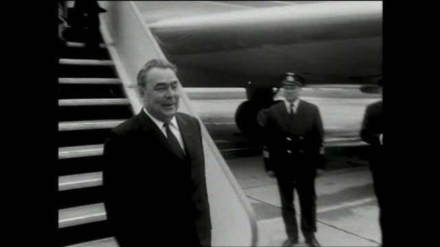 officials in suits walking and talking in front of crowd of people in the square; russian official descending steps from a plane and greeted by men;... - レオニード・ブレジネフ点の映像素材/bロール