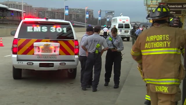 officials stand together by truck outside terminal in reagan national airport. zoom out to firemen and police officials responding on scene to the... - ロナルド レーガン ワシントン国際空港点の映像素材/bロール