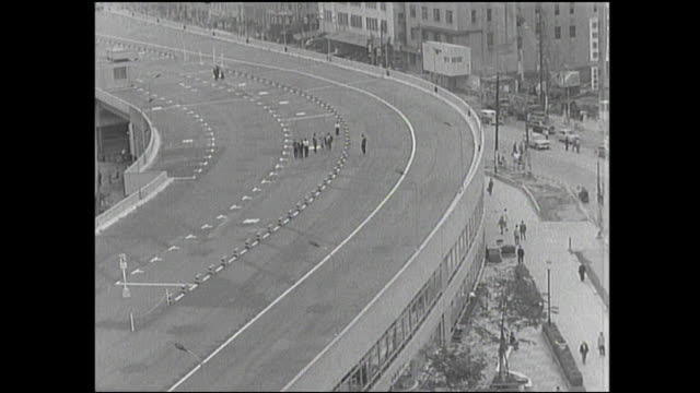 officials walk on the elevated newly finished tokyo expressway. - 1950~1959年点の映像素材/bロール