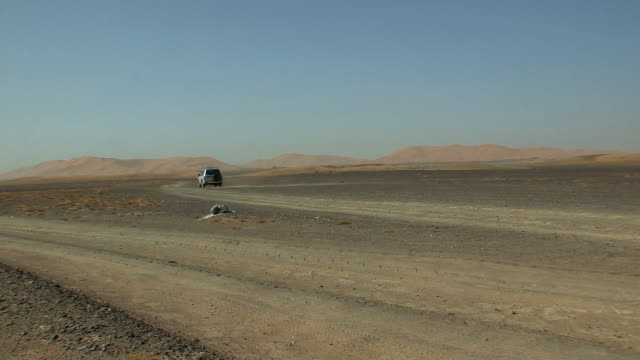 ws off-road car driving through desert, merzouga, morocco - ciglio della strada video stock e b–roll