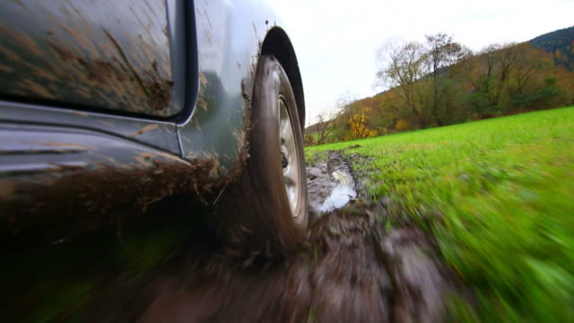 hd off-road vehicle driving through mud pov - dirt track stock videos & royalty-free footage
