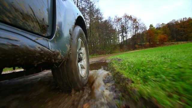 Fuera de carretera de conducción en Mud punto de vista a través de un vehículo