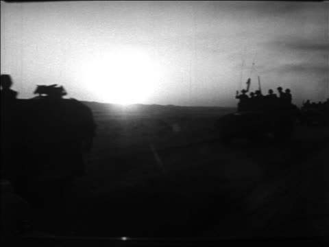 silhouette offroad vehicles with israeli soldiers on desert road at sunset / six day war / newsreel - sechstagekrieg stock-videos und b-roll-filmmaterial