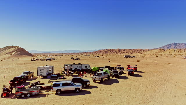 off-roader encampment of suvs and motorhomes in circle the wagon formation around picnic table and chairs in california desert campground - off road racing stock videos & royalty-free footage