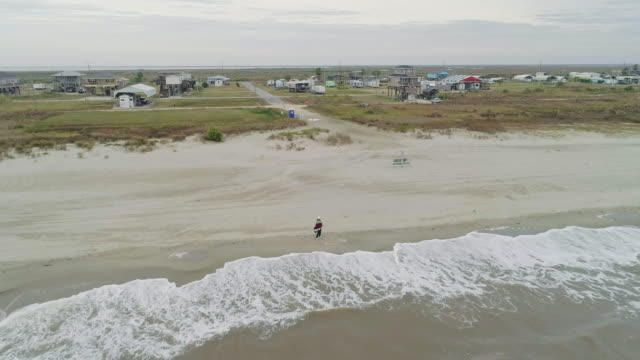 off-season vacations. mature woman, tourist, walking on the sandy beach of gulf of mexico in holly beach, cameron, louisiana. cold windy weather and overcast sky. aerial drone video with the forward and ascending camera motion. - louisiana stock videos & royalty-free footage