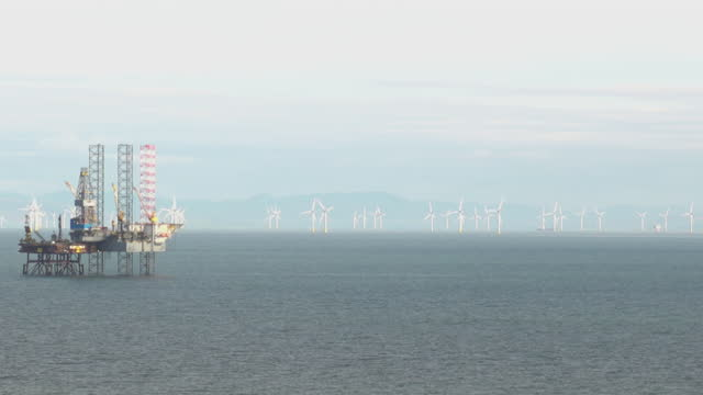 offshore gas platforms with wind farm in background - power supply stock videos & royalty-free footage