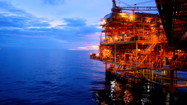 vídeos de stock e filmes b-roll de offshore oil and gas platform, central processing platform in sunset time produced raw gases and condensate or crude oil then sent gas to onshore refinery - indústria petrolífera