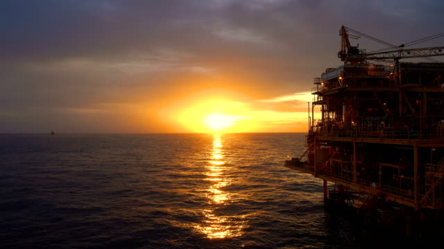 offshore oil and gas platform, central processing platform in sunset time produced raw gases and condensate or crude oil then sent gas to onshore refinery - petrol stock videos & royalty-free footage