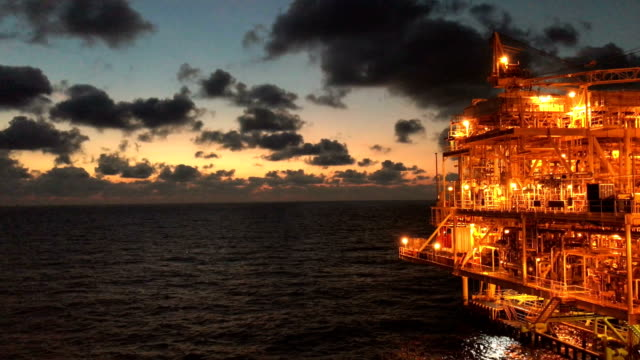vídeos de stock e filmes b-roll de offshore oil and gas platform, central processing platform in sunset time produced raw gases and condensate or crude oil then sent gas to onshore refinery - perfurar