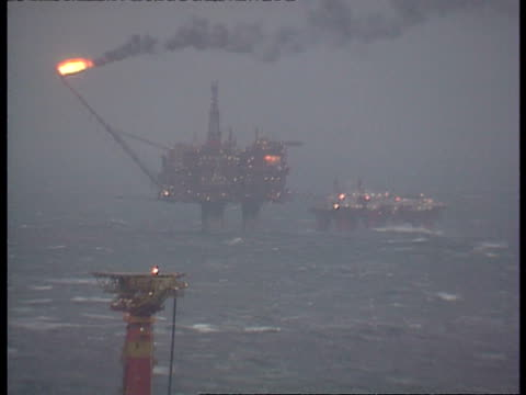 wa offshore oil rig in rough sea, flames escaping from exhaust stack, zooms out - 石油産業点の映像素材/bロール