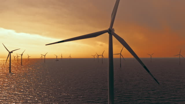 aerial offshore turbines rotating in sunset - turbine stock videos & royalty-free footage