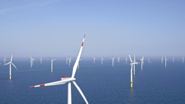 aerial offshore wind farm producing green energy - tilt down stock videos & royalty-free footage