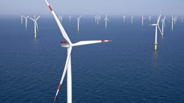 aerial offshore wind farm producing renewable energy - wind turbine stock videos & royalty-free footage