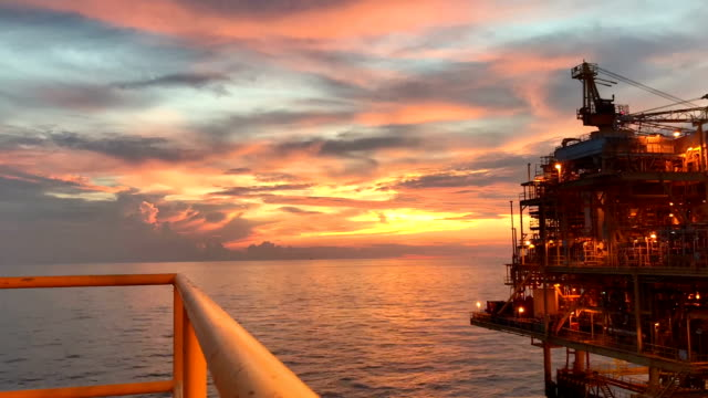 offshortimelapse footage of oil and gas platform with panning shot with sun set and beautiful clouds in the evening for oil and gas industry business concept.e - crane construction machinery stock videos & royalty-free footage