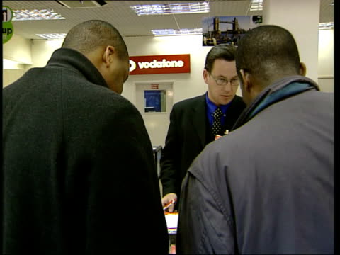 oftel report on mobile phones; itn england: london int tms mobile phones on display in cabinet as customers examine side customers salesman mbv men... - display cabinet stock videos & royalty-free footage