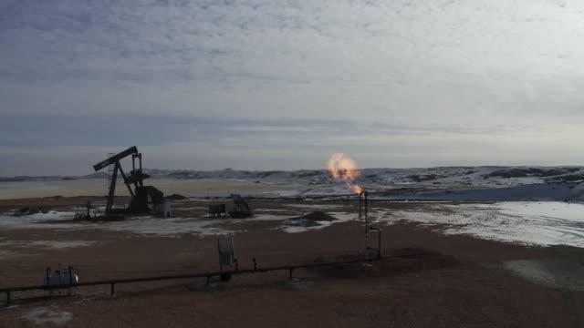 oil and gas fracking and drilling rig/pump jack in williston, north dakota. - 燃焼煙突点の映像素材/bロール
