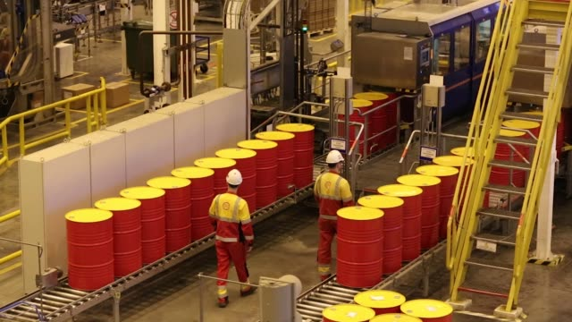 oil drums containing lubricant oil sit on a conveyor belt as they are prepared for shipping at the royal dutch shell plc lubricants blending plant in... - lubrication stock videos & royalty-free footage