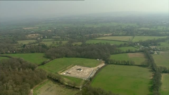 vidéos et rushes de oil field discovery under surrey and sussex air view drilling site and surrounding countryside - entourer