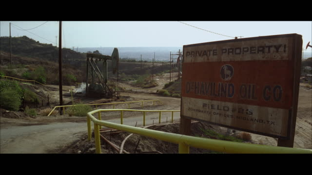ws oil field with old sign, car driving past - trespassing stock videos & royalty-free footage