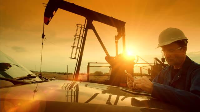 vídeos de stock e filmes b-roll de oil field worker at oil pump jack - bomba petrolífera