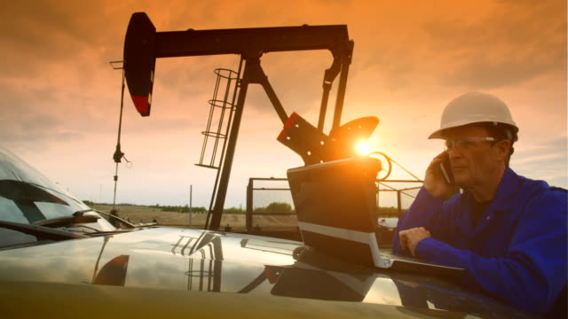 oil field worker at oil pump jack - industria petrolifera video stock e b–roll