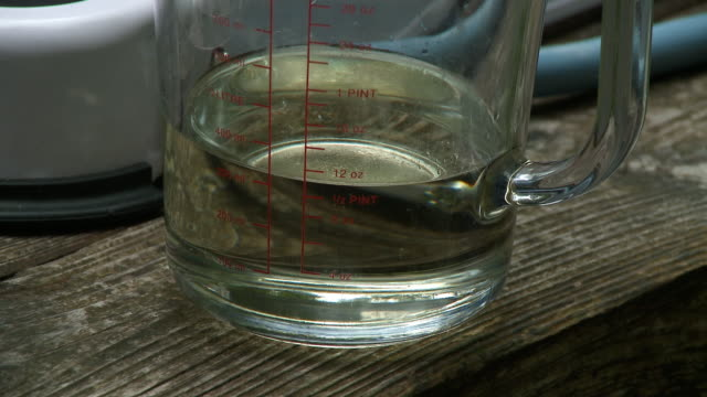 vídeos de stock e filmes b-roll de oil in measuring cup - mesa de piquenique