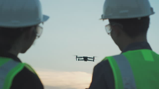 oil industry supervisors and operator inspecting construction building site flying with drone - construction industry stock videos & royalty-free footage