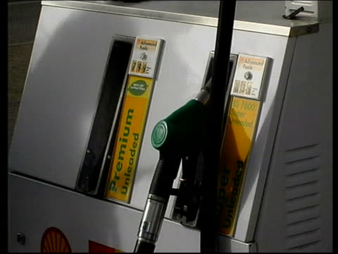 oil industry warns of rise in petrol prices la price board outside petrol station woman using petrol pump cs display on pump nozzle for unleaded... - unleaded stock videos and b-roll footage