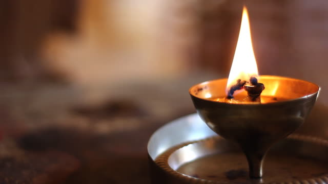 Oil lamp burning in hindu temple, India