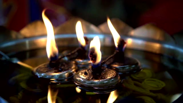 vídeos de stock e filmes b-roll de oil lamp with flame in thai temple in slow motion. - incenso