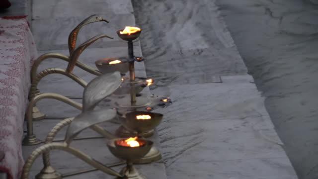 ms oil lamps at ganges river bank / rishikesh, uttarakhand, india - acqua santa video stock e b–roll