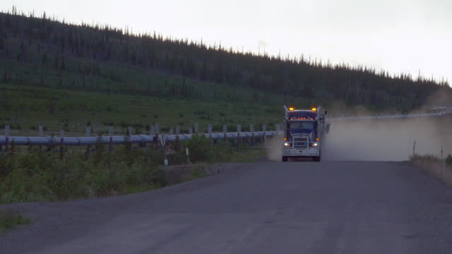 oil pipeline and truck driving on alaska dalton highway - articulated lorry stock videos & royalty-free footage