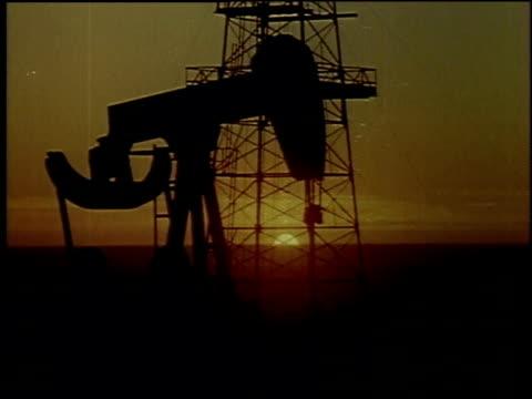 1957 montage oil pump jack and drilling rig at sunset or sunrise / new york city, new york, united states - 1957 bildbanksvideor och videomaterial från bakom kulisserna