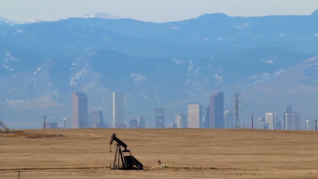 oil pump jack downtown denver colorado rocky mountains - denver stock videos and b-roll footage