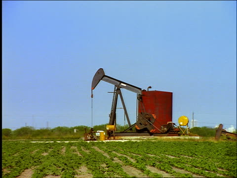 oil pump with green field in foreground / galveston, texas - cinematografi bildbanksvideor och videomaterial från bakom kulisserna